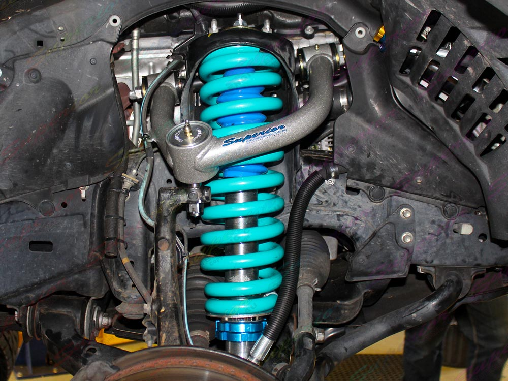 Closeup view of a Profender 4x4 Adjustable Remote Reservoir Strut, Blue Coil Spring and Superior Engineering Upper Control Arm fitted to the a 200 Series Toyota Landcruiser